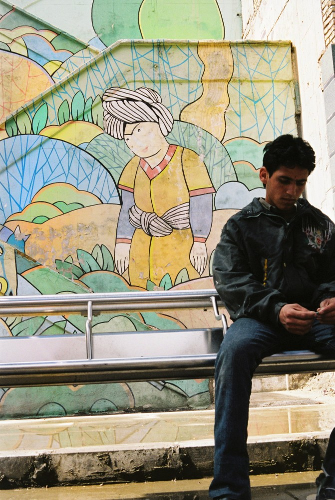 Young man at bus stop Tehran by Anna Sande